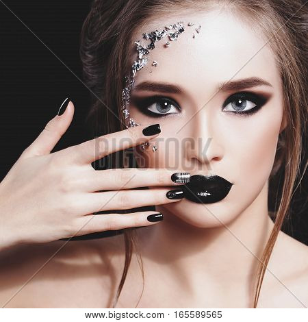 Beauty Woman Portrait. Professional Makeup and Manicure with siver foil glitter, smokey eyes. Black colors. Copy-space. Pastel toned