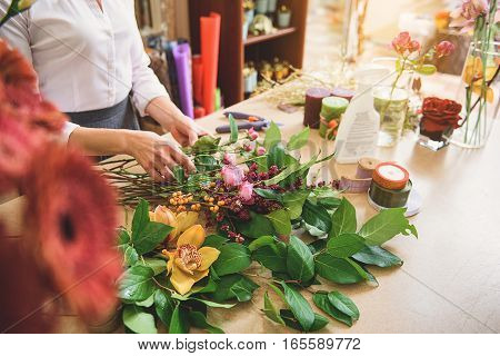 Skillful woman is touching various flowers and making bouquet of it. Close up of her arms over the desk