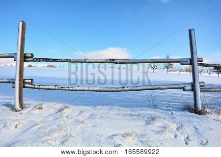 Look by a wooden fence on a field in winter with snow and blue sky