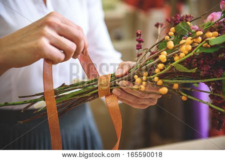 Close up of female hands rolling by ribbon bouquet of plants