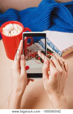 woman taking photo of hot chocolate on wooden table with love blank card for valentines day concept,