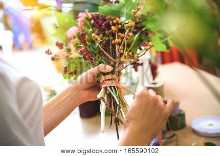 Skillful florist is binding flowers by ribbon carefully. Close up of her arms