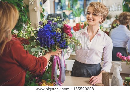 Friendly female florist is giving self-made bouquet to client. She is standing at counter and smiling