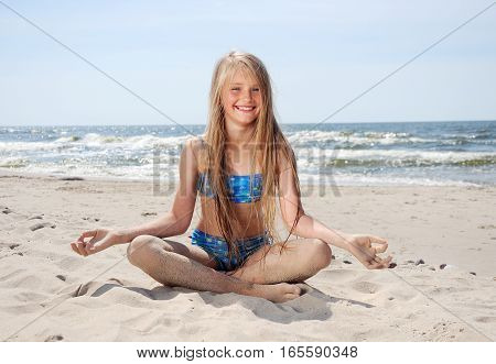 Little cute girl sitting on beach sunny day