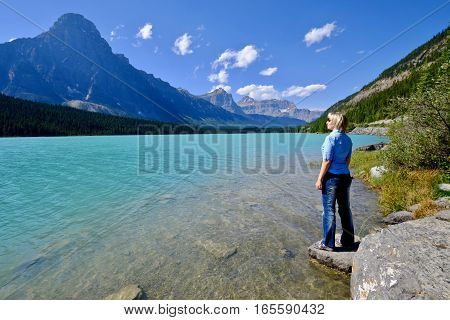 Woman by blue lake in rocky mountains. Waterfowl lake. Canadian Rockies. Banff National Park. British Columbia. Canada.