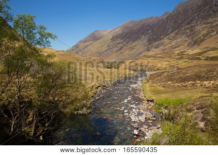 Glencoe river Clachaig Scotland UK with mountains in Scottish Highlands in spring with people