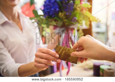 Close up of female arm paying for bouquet in shop. Woman is handing credit card to florist