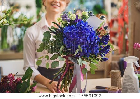 This will be great present. Cheerful woman is showing flowers with card to camera. She is standing at counter in shop and laughing