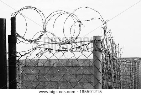 Secured area with barbed wire and fence black and white