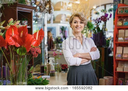 I like my work. Happy female florist is standing in her store and smiling. Her arms are crossed with confidence