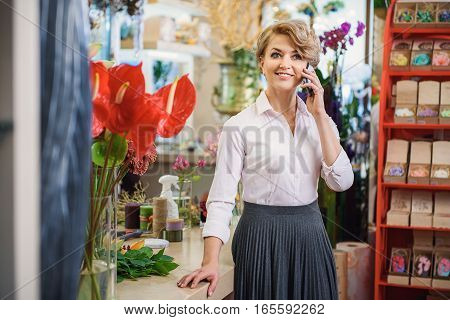 Joyful female florist is talking on mobile phone and laughing. She is standing near table in her store