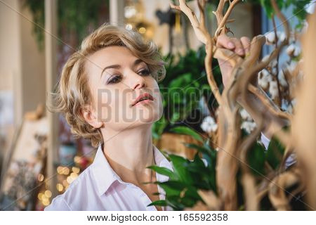 Skillful female florist is touching wood decoration and looking at it with concentration