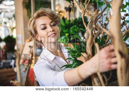 Happy woman is working in flower shop. She is touching wooden object and smiling