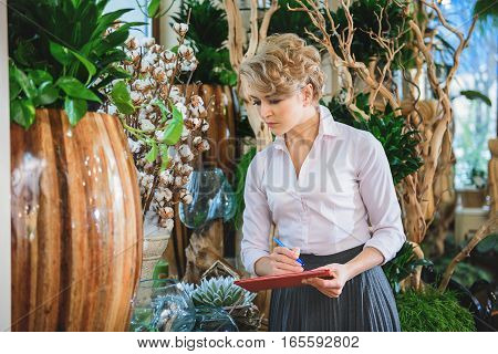 Skillful female florist is checking flowerpots in her shop. She is standing and making notes with concentration