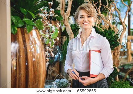 Happy woman is standing near plants in her flower shop. She is carrying folder of papers with pen and smiling