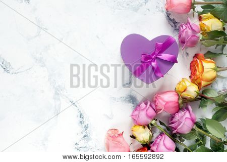Purple and yellow roses, box present on white background. Overhead view with copy space