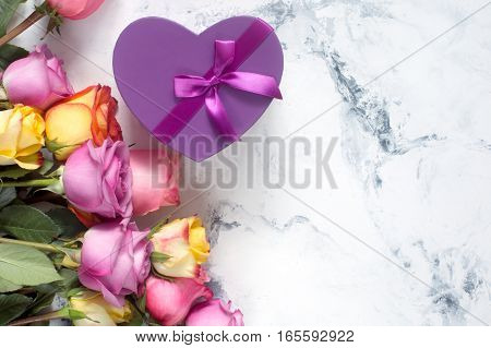 Purple and yellow roses, box present on white background. Overhead view with copy space. Top view