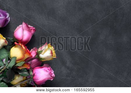 Purple and yellow roses, box present on black background. Overhead view with copy space