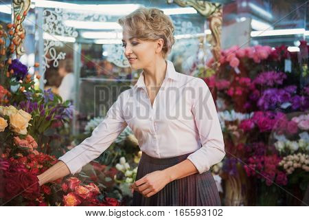 Joyful woman is working in her flower shop. She is taking rose and smiling