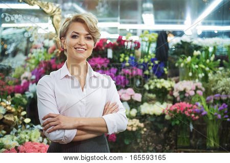 Come in and choose any bouquet. Confident female florist is standing in her store and laughing. She is looking through showcase with joy