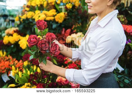 Joyful woman is making bouquet of red roses with aspiration. She is standing in her shop and smiling