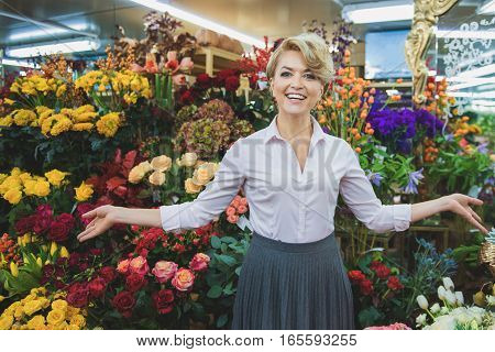 Happy female florist is presenting wide selection of flowers in her shop. She is stretching arms sideways and laughing