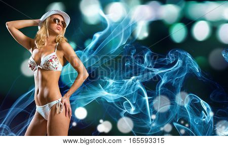 Young beautiful girl in bikini and hat on blurred lights background
