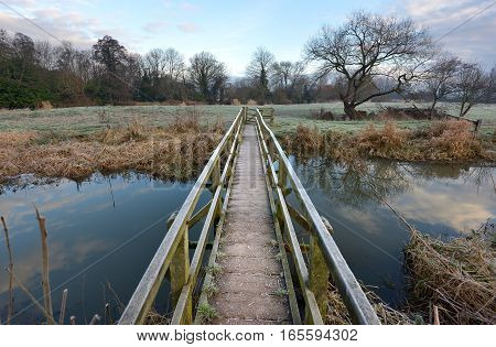 Wooden Footbridge Over A Small River In Winter