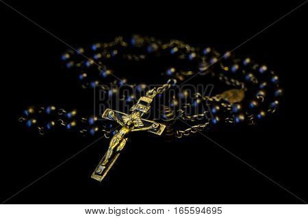 Gold christian crucifix with wooden rosary beads