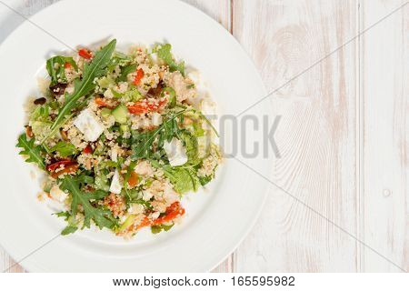 Overhead shot of a couscous salad on a white plate placed on a white wood background. The salad ingredients consist of rocket feta cheese pinenuts and roasted peppers. Copyspace to the right of the frame