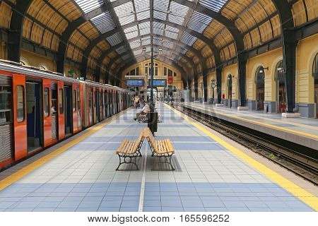 PIRAEUS GREECE - MAY 04: Train Station in Piraeus on MAY 04 2015. Commuters Waiting for Train at Platform in Piraeus Greece.