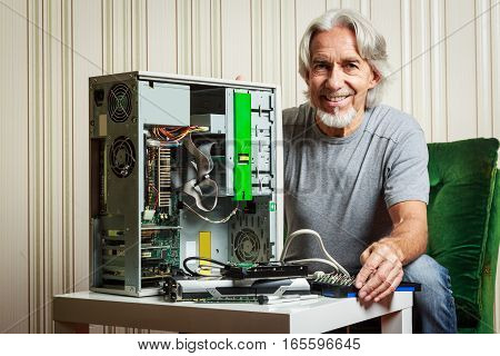 This senior man is not afraid of new tchnology and is assembling a desktop computer