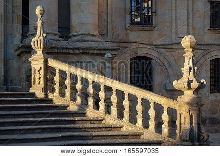 Sunlit stone stairway of the Mosteiro de San Martino Pinario in Santiago de Compostela, Galicia, Spain
