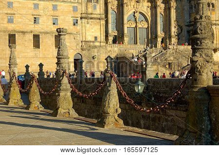 Sunlit stone balusters and iron chain on the Square Obradoiro in Santiago de Compostela, Galicia, Spain
