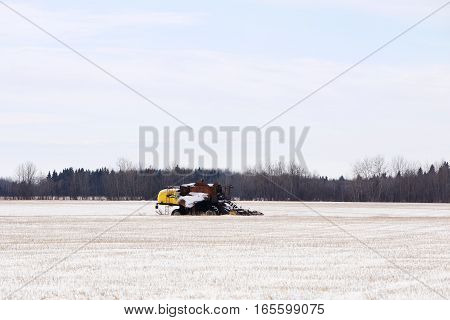 A harvester with the front half burned parked in a field of crop stubble dusted with snow in a rural agricultural landscape