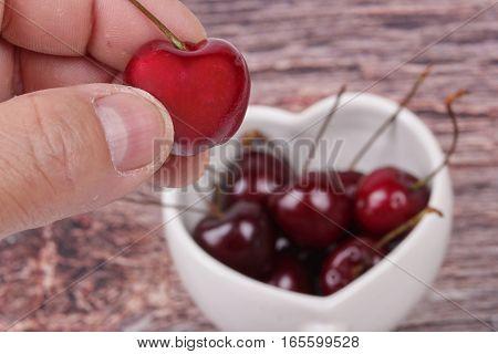 Hand-picked Cherriy And Cherries In Heart-shaped Mug On Wooden.