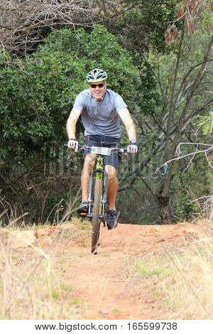 Smiling Man Enjoying Outdoors Ride At Mountain Bike Race