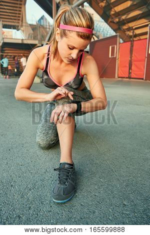Young girl timing her workout performance with her touchscreen device and persuing fitness goals