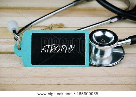 Stethoscope and wooden tag written with Atrophy on wooden background. Medical and Healthcare concept.