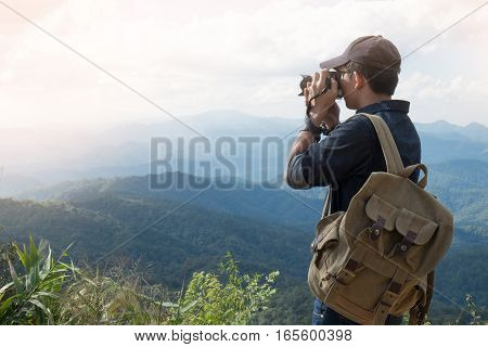 Young professional travrler man with camera shooting outdoor fantastic mountain landscape.