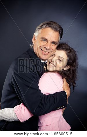 studio shot of a hugging business team after just shaking hands for so many years, they felt like they were ready for the next step in their business relationship . or it could also be the business dad hugging his daugher.