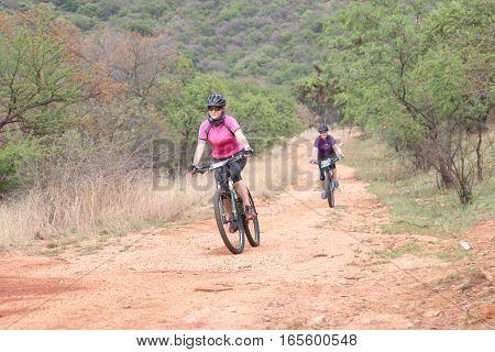 Middle Aged Women Enjoying Outdoors Ride At Mountain Bike Race