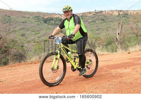 Smiling Aged Man Enjoying Outdoors Ride At Mountain Bike Race
