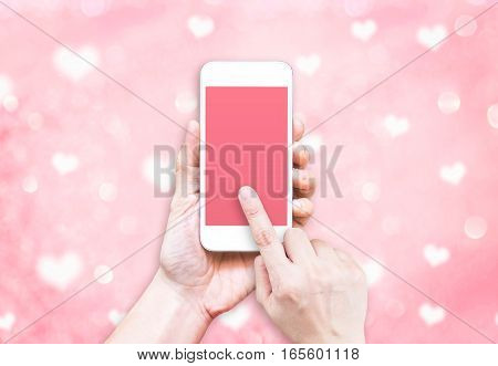 Hand Holding Mobile Phone With Finger Touch On Pink Screen On Blur Pastel Pink Heart Bokeh Light Bac