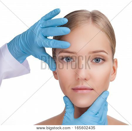 Surgeon in a blue gloves touching the face of a beautiful woman by hands, closeup