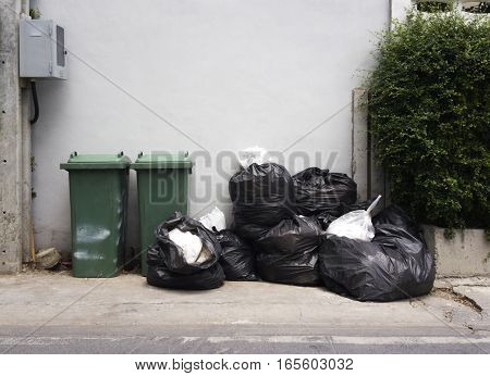 Green dumpsters and Black garbage bags Outdoors