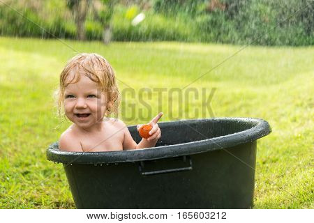 Happy blonde baby boy sitting in a basin with water when it rains. The curly-haired child on green grass in the water tank. It shows a finger.