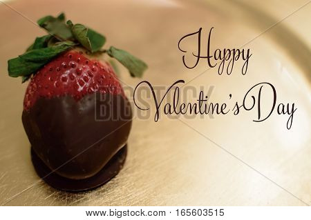 Happy Valentine's Day greeting decadent sweet food strawberry dipped in rich chocolate heart shape for social network share image or  Valentine's message with copy space on gold background