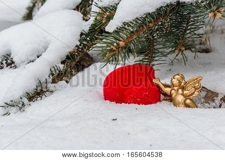 Heart-shaped gift box for wedding ring and gold color angel figure in the snow against the background of snow-covered fir branches