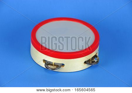 kids musical tambourine isolated on blue background